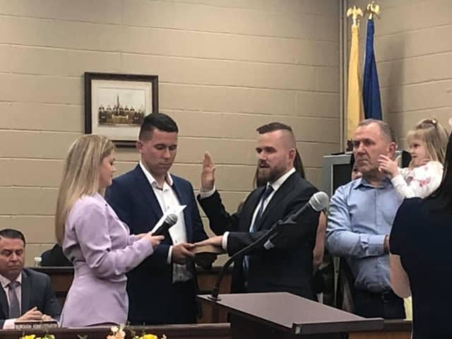 Daniel Golabek being sworn in by borough clerk Erin Delaney. His brother and school board member, Jakub, holds the bible.