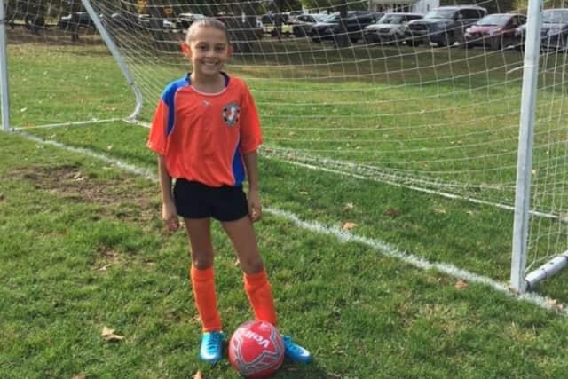 Arianna Muti, 9, dressed in full soccer gear.