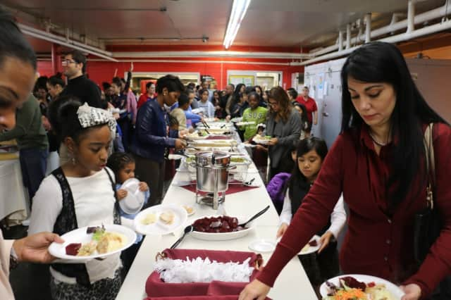 Guests help themselves at the buffet line during last year's Feast of Giving, run by iLearn Schools.