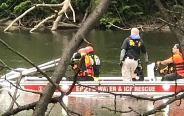 Elmwood Park firefighters return body (unseen in photo) to the shore.