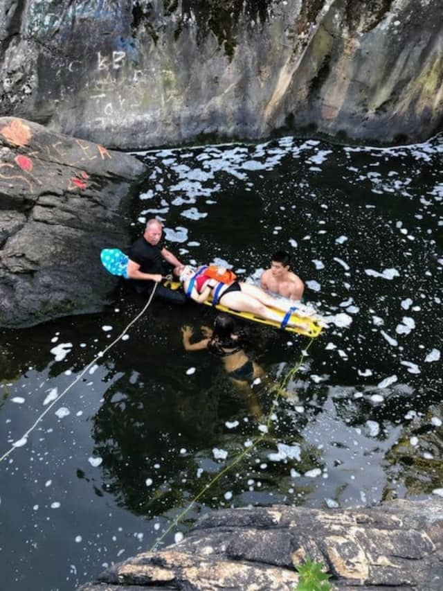 A woman was saved by numerous first responders after falling 35-feet onto rocks below.
