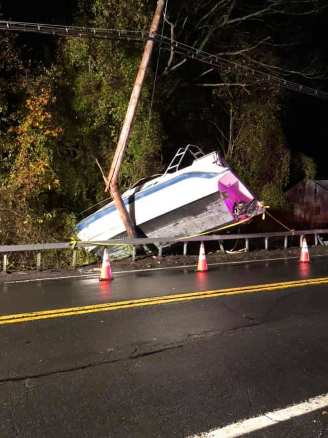 A boat being towed by a U-Haul box truck broke loose and slammed into a utility pole.