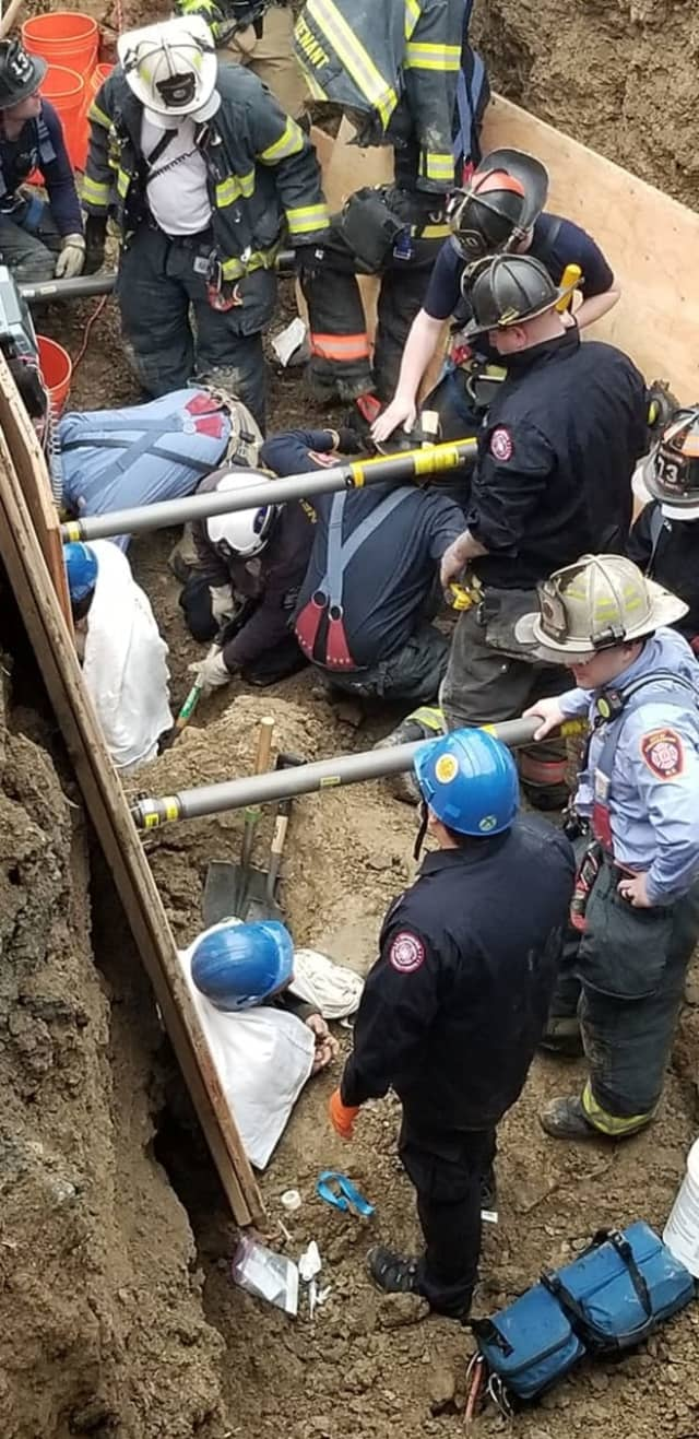 Two men were rescued after being trapped in 10-feet of dirt following a trench collapse.