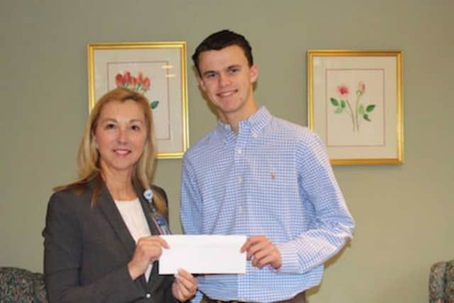 Mason Jennings, a senior at Fairfield Ludlowe High School, presents Dr. Donna Twist, executive director of the Norma Pfriem Breast Center at Bridgeport Hospital, with a $500 donation.