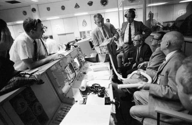"""Working the problem:""  Deke Slayton (checked jacket) shows the adapter devised to remove excess carbon dioxide from the Apollo 13 Lunar Module cabin, which was dramatized in the movie ""Apollo 13, based on ""Lost Moon"" by Jim Lovell and Jeffrey Kluger. From left, members of Slayton's audience are flight director Milton L. Windler; deputy director/flight operations Howard W. Tindall; director/flight operations Sigurd A Sjoberg; deputy director/Manned Spaceflight Center Christopher C. Kraft; and director/Manned Spaceflight Center Robert R. Gilruth. Photograph courtesy of NASA."