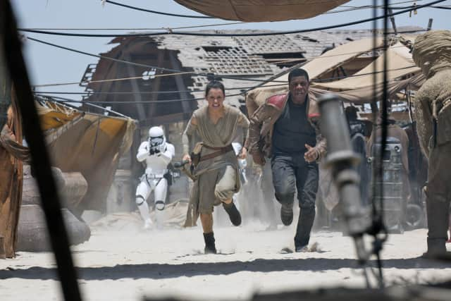 "Rey (Daisy Ridley) and Finn (John Boyega) take fire from stormtroopers in a scene from ""Star Wars: The Force Awakens."""