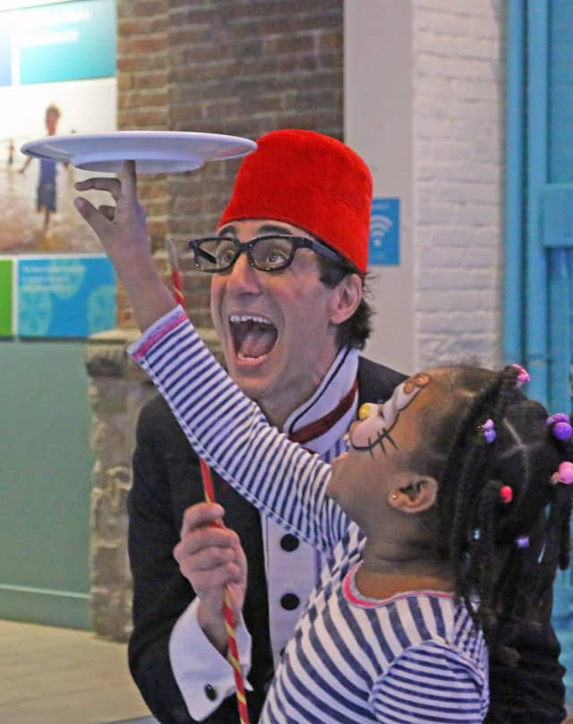 Comedian/juggler Peter Straus clowns with a young guest and a spinning plate during last year's New Year's Eve celebration at The Maritime Aquarium at Norwalk.