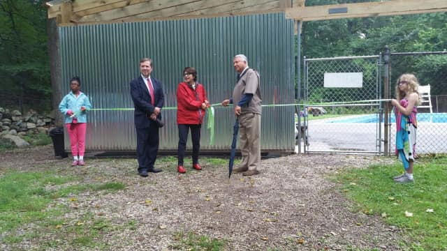 Girl Scouts of the USA's CEO Sylvia Acevedo cuts the ribbon with two campers at the new Camp Aspetuck shower house in Weston. It was made possible by a donation from the Norma F. Pfriem Foundation. Trustees Paul Miller and Matthew Woods look on.