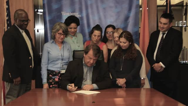 Westchester County Executive George Latimer signing the bill.