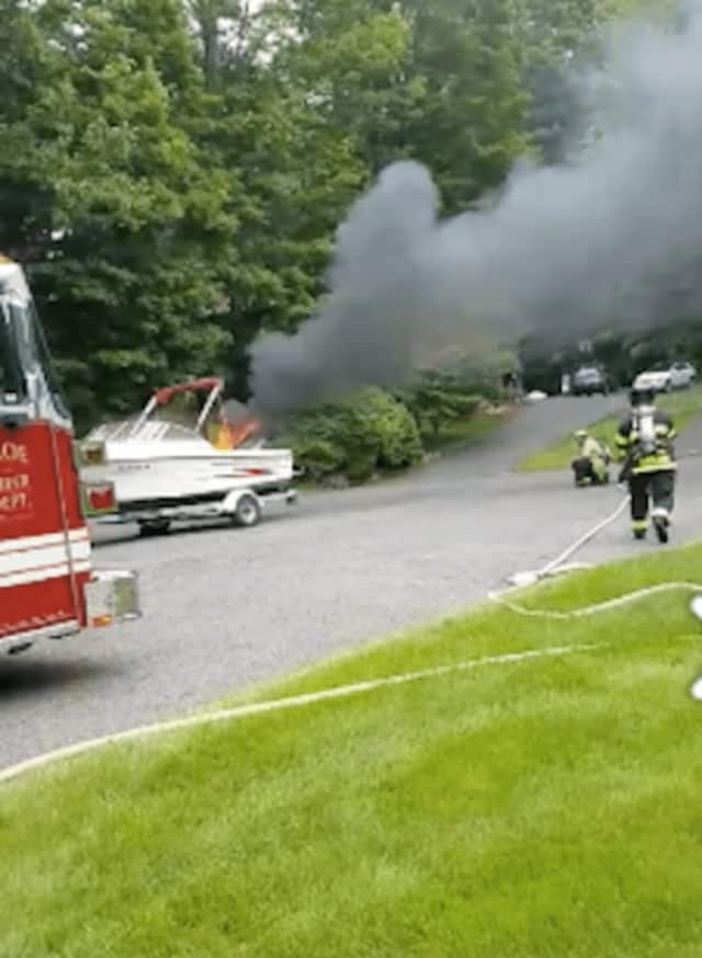 The burning boat was on a trailer at a home on Christiana Drive in Trumbull on Saturday.