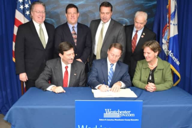 Westchester County Executive Robert P. Astorino signs the $1.8 billion budget on Friday, Dec. 18, as members of the budget coalition look on.