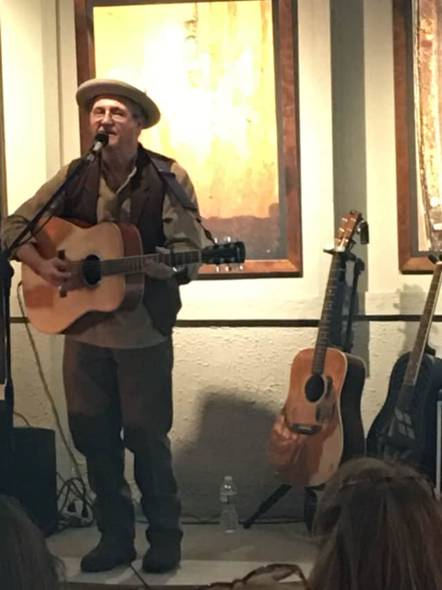 Blues musician Phil Dollard plays at a recent exhibit of photographs by Robert Olsson in Ossining.