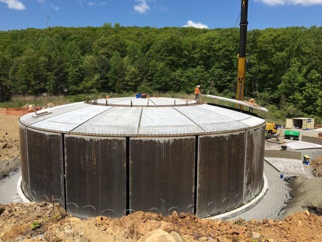 A construction crane drops the final dome panel in place on the Eureka water tank in Bethel.