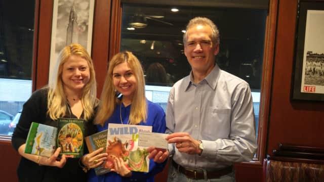 Rotarian Bill Ziegler presents a $500 check to ACS teachers Lisa Compel and Jill Miller.