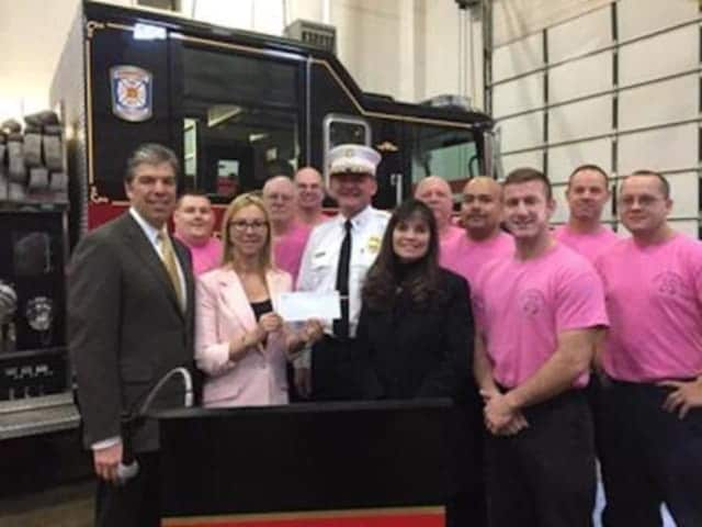 Dr. Donna Twist, executive director of Norma Pfriem Breast Center, holding the check tor $6,363 donated by Bridgeport Firefighters. Bridgeport Fire Chief Richard Thode, in white, is on the right.