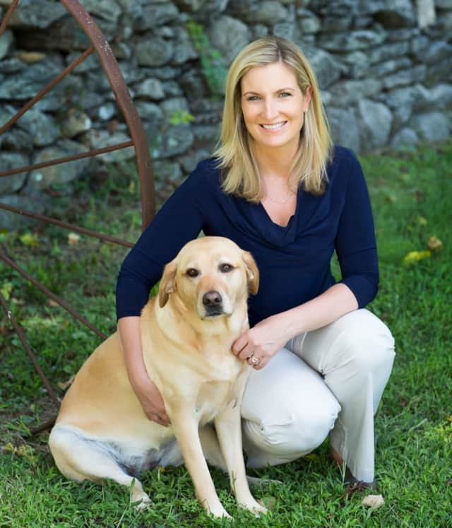 Jennifer Hill, the president of Wilton-based Canine Company, with her yellow lab, Chloe.