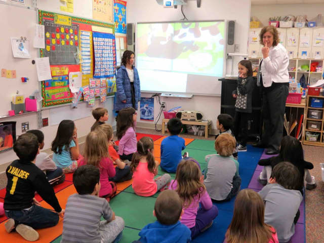 """Carrie E. Tompkins Elementary School fourth-graders Tori and Sofia, alongside sign language interpreter Christine Fico, read the sign-language book """"There's a Story in My Head"""" to teach kindergarten students at the Croton school."""