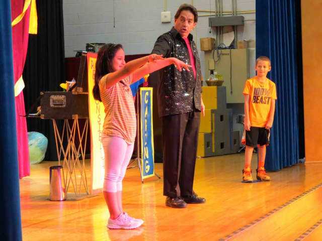 "Carrie E. Tompkins Elementary School students Ingrid, left, and Max, aided James ""Magic Jim"" Vagias in performing magic tricks during his show that encouraged them to embrace the themes of respect, responsibility and caring."