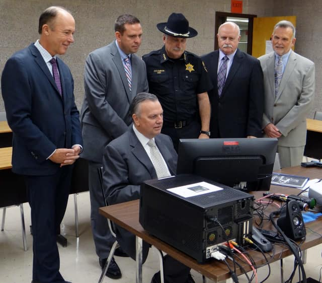 SUNY Orange Criminal Justice Professor Robert Cacciatore (seated), demonstrates the College's new Response to Resistance Simulator.