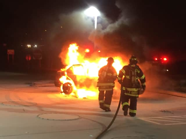 Fairfield firefighters extinguish a burning car about 50 feet from the gas pumps at the Cumberland Farms at 975 Kings Highway E. on Sunday morning.