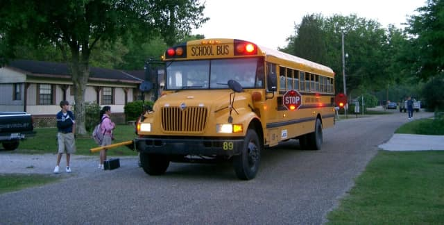 A school bus picks up kids.