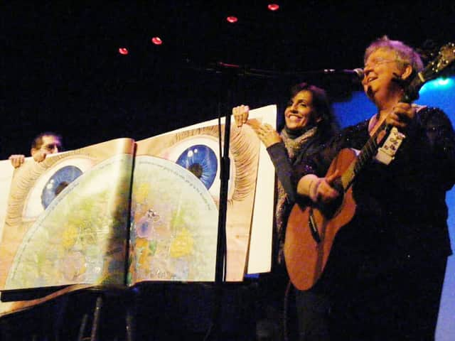 "Piermont's Betsy Franco Feeney and another audience member hold the giant copy of the children's book ""Amoeba Hop"" at Hurdy Gurdy's in Fair Lawn, N.J. while folksinger Christine Lavin plays."