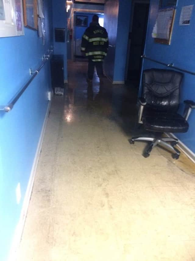 A member of the Clarkstown Fire Department surveys the damage at the Spring Valley Rest Home in Nanuet after flooding on Monday afternoon.