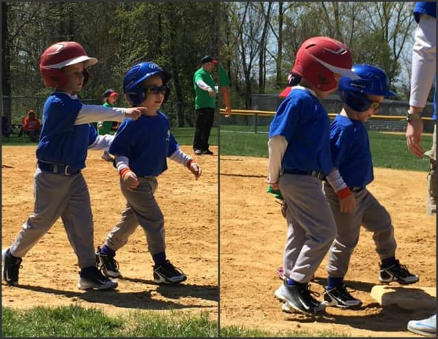 Marcello helps Frankie, 5, around the bases at their Washington Township T-ball game.