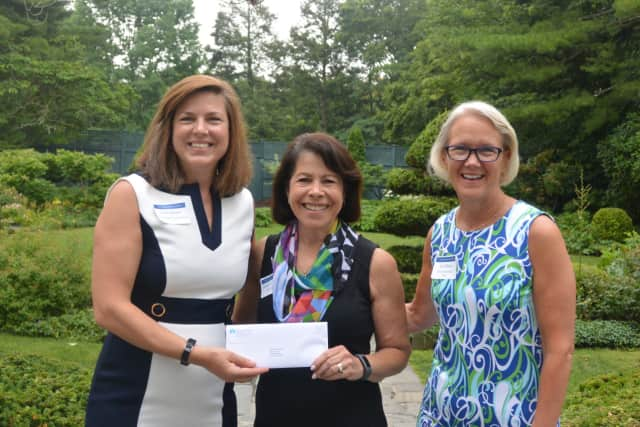 Shari Shapiro, executive director of Kids in Crisis, center, receives a check from Carrie Bernier (left) and Amy Wilkinson (right) of The Community Fund of Darien.