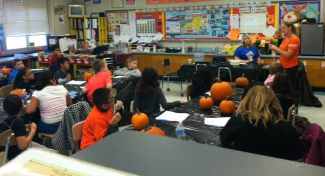 Children prepare to carve their pumpkins at Cottle Elementary