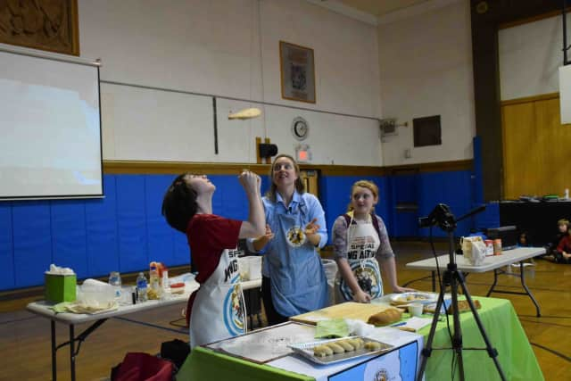 Amy Driscoll of the Vermont-based King Arthur Flour Co. shows seventh-graders at the Pierre Van Cortlandt Middle School in Croton-on-Hudson how to toss pizza dough. Doing the tossing is student Charlie Azalone . At right is student Desiree Cilentl.