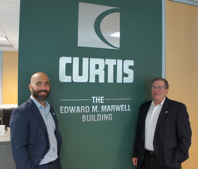 Nick Marwell, left, and his father Stuart Marwell, right, stand in front of the Curtis dedication to company founder Edward M. Marwell.