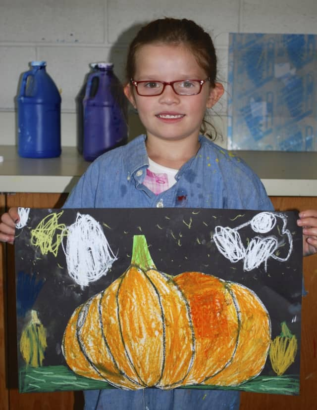 Olivia Sapper holds up her pastel pumpkin from last year's 'Halloween Fun for Your Little One' at the Darien Arts Center.