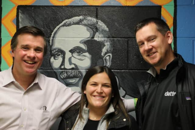 Joe Gallagher, Carver, Director of Philanthropy; Kate Scully, Datto Event Planner; Nicholas Hagen, Sales Manager-Midwest. Image taken at Carver Community Center; drawing of Carver's namesake, George Washington Carver on wall in background.