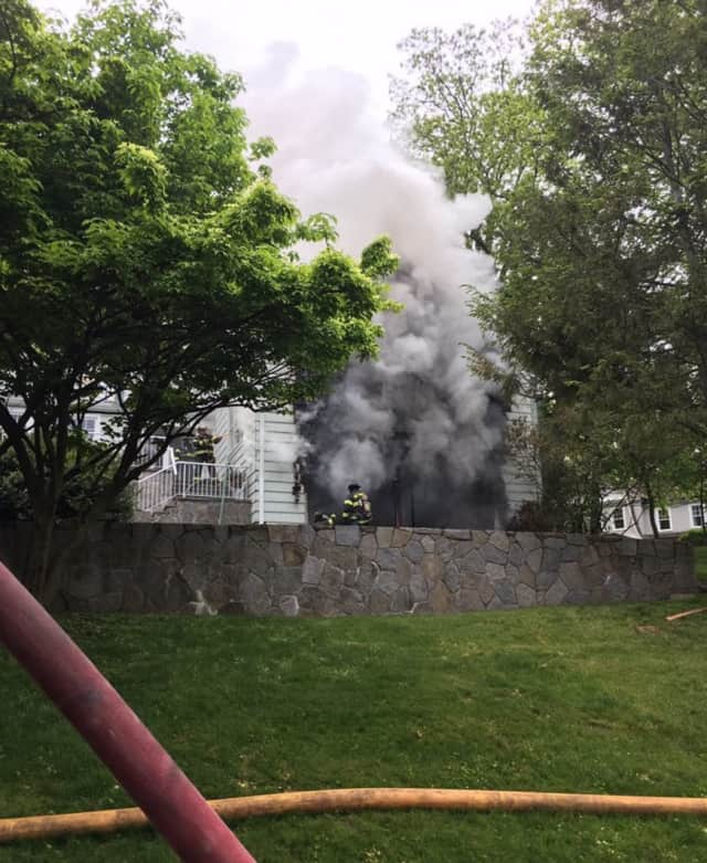 A smokey fire burns at a home on Perkley Lane in Greenwich on Monday morning.