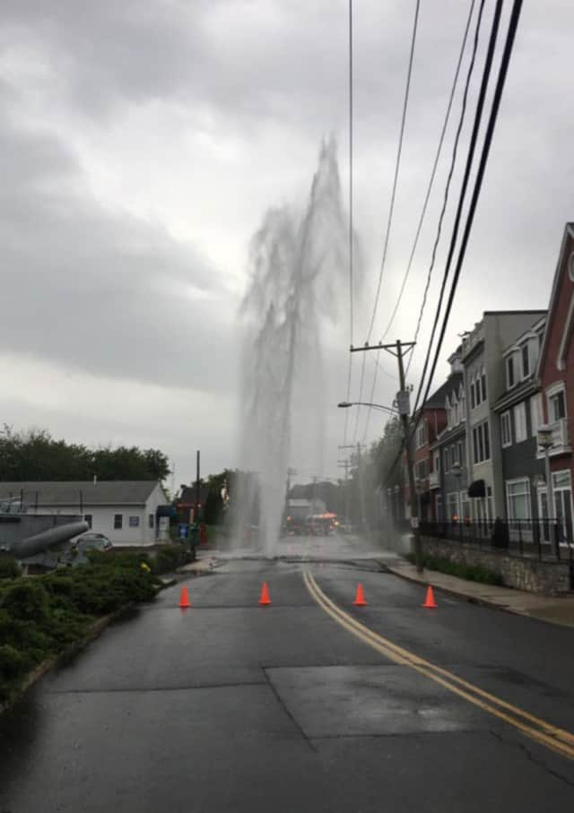 Water shoots more than three stories into the air after a water main break on Helwig Street in Milford late Sunday afternoon.