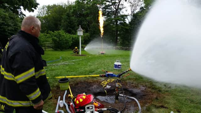 New Canaan Fire Department members work to burn off a leaking underground propane tank.