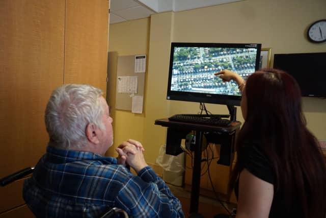 A resident at the Jewish Home at Rockleigh reminisces about his childhood neighborhood while viewing it with a member of the Recreation staff using one of the iN2L units she brought to his room.