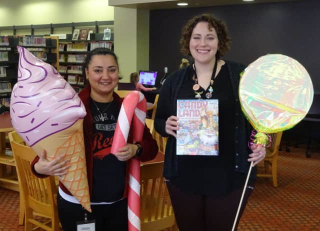 Rola Salloum and Caitlin Siciliano, who both work at the Mahwah Public Library, pose with some of the props that will be used for the life-sized Candy Land game.