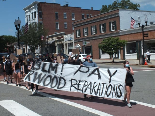 "Ridgewood 4 Black Liberation members carry banner that says: ""BLM! PAY RWOOD REPARATIONS"""