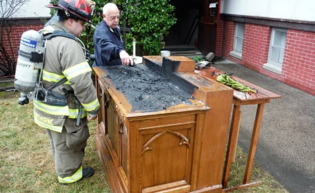 Firefighters removed the still-smoking altar from the church.