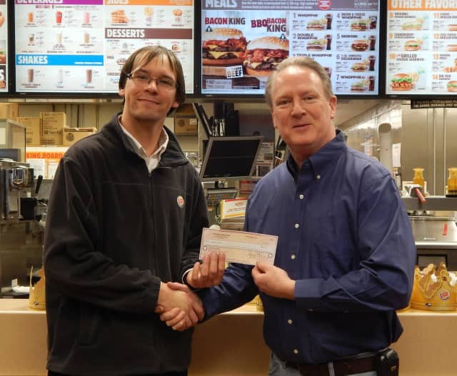 """Matthew Fitzgerald, Burger King assistant manager, presents """"Dining to Donate"""" donation to David Humphrey of Yorktown Community Help."""