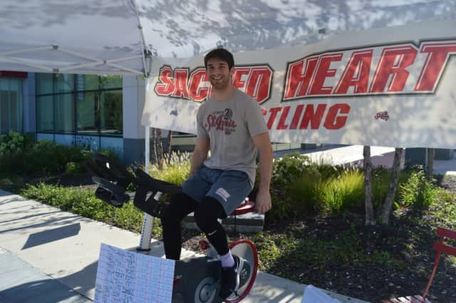 Sacred Heart University wrestling team captain Matt Fisher takes a turn on the stationary bike to raise funds for the Division 1 Pioneers.