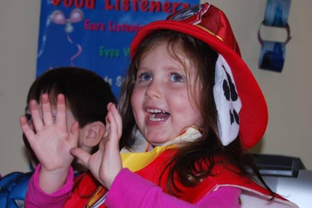 Emma Williams sings as the children at the Methodist Family Center Preschool in Darien celebrate Halloween.