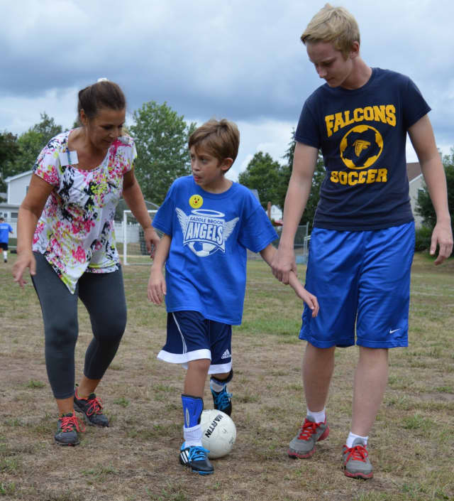 A young athlete with special needs dribbles up the field with his mother and a Saddle Brook Angels volunteer.