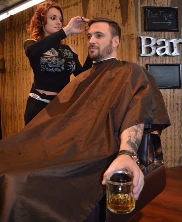 Christine Modica cuts Jordan G's hair as he sips whiskey at Stag House in Glen Rock.