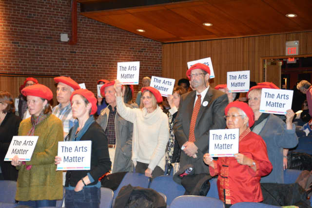 Opponents of a proposed cut in arts funding for the 2016 Westchester County budget attend a hearing with red berets and signs.