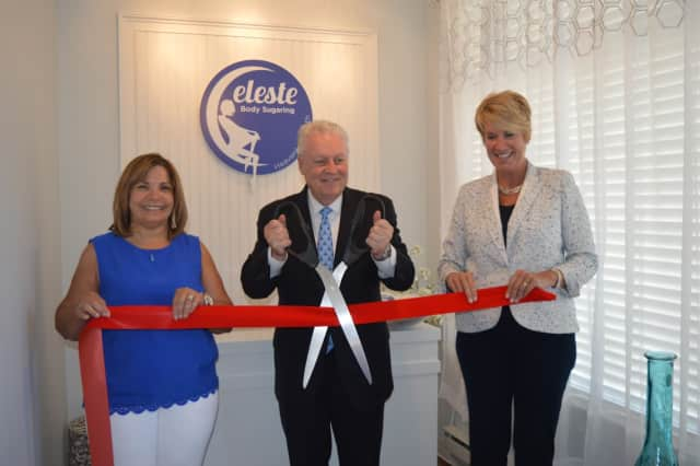 Fairfield First Selectman Michael Tetreau cuts the ribbon at Celeste Body Sugaring, while owner Alda Membrino and State Rep. Laura Devlin look on during the grand-opening ceremony.
