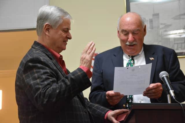 Mount Kisco Library Board Trustee Bernie Seiler, left, takes his oath of office, which is administered by Mayor Michael Cindrich.