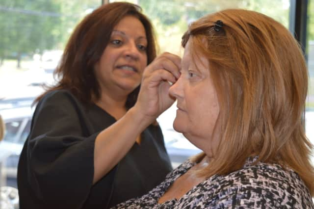 Teaneck salon owner Lillian Lee helps Patty, who has breast cancer, with her makeup before a wedding.